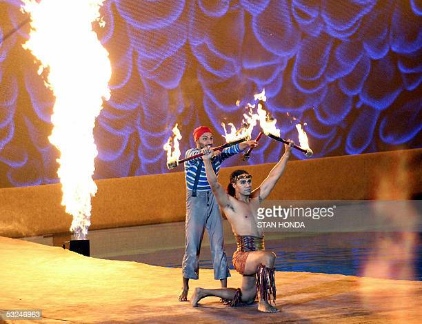 Cirque du Soleil performers holds sticks on fire at the opening ceremonies 16 July 2005 for the 2005 XI FINA World Championships that will take place...