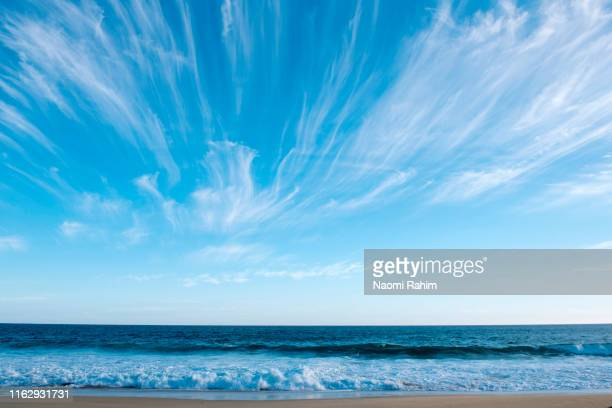 cirrus clouds over a surf beach at san remo, australia - bass strait stock pictures, royalty-free photos & images