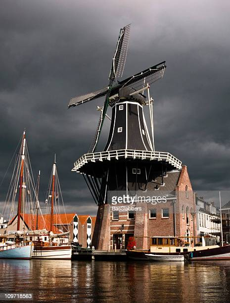 cities; dutch windmill near harbor with stormy sky - haarlem stock photos and pictures
