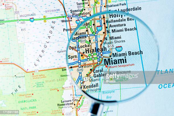 cities under magnifying glass on map: miami - us state border stock photos and pictures