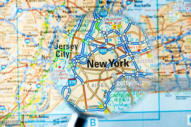 Cities under magnifying glass on map: New York