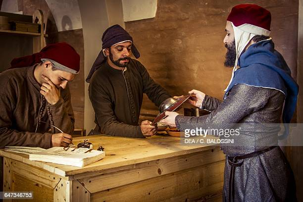 Citizen bringing a buckler to pawn at the apothecary run by Diotaiuti di Cecco Imola Italy mid14th century Historical reenactment