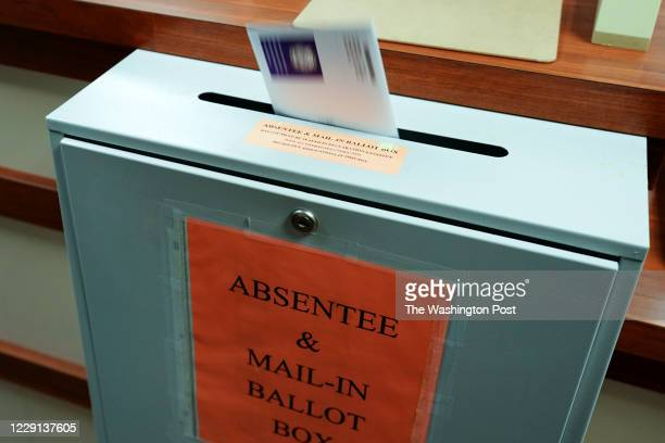 Citizen deposits a ballot into a box at the county clerk's office in Erie, Pennsylvania, on October 15, 2020.