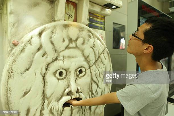 A citizen handles a fortunetelling machine at an underground mall in People's Square on August 4 2016 in Shanghai China Only three coins one can...