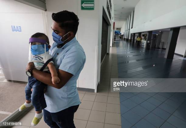 Citizen holds his toddler while waiting to leave Nicaragua after the US embassy sent an alert encouraging its citizens to consider leaving the...