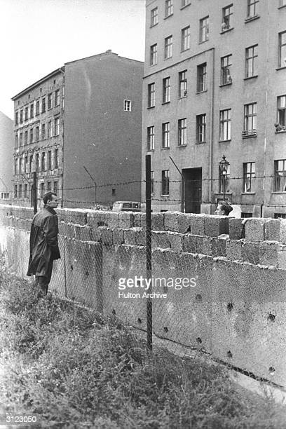 A citizen of East Berlin peers through barbed wire at a West Berliner over the Berlin Wall Berlin Germany 1960s The mass immigration of Germans from...
