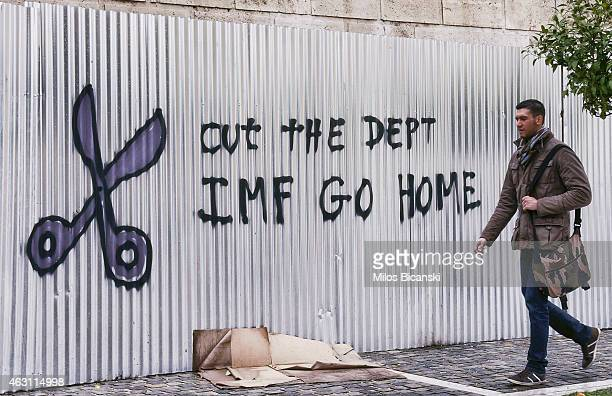 A citizen passes by graffiti against the IMF on February 10 2015 in Athens Greece The new Greek antiausterity government is seeking a renegotiation...