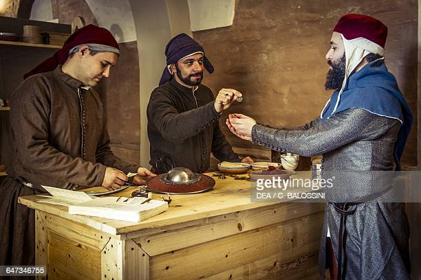 Citizen receiving money after pawning a buckler at the apothecary run by Diotaiuti di Cecco Imola Italy mid14th century Historical reenactment