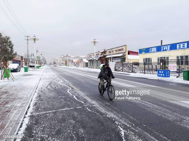 Citizen rides a bike in snow in Mohe City, Heilongjiang Province, China, April 19, 2020.- PHOTOGRAPH BY Costfoto / Barcroft Studios / Future...