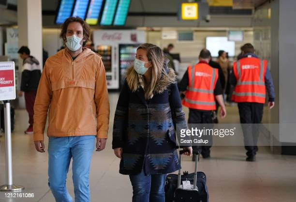 Citizen Sarah McNeil, and friend Nick Goddard wear protective masks as they make their way to Sarah's departure gate to return to the United States...