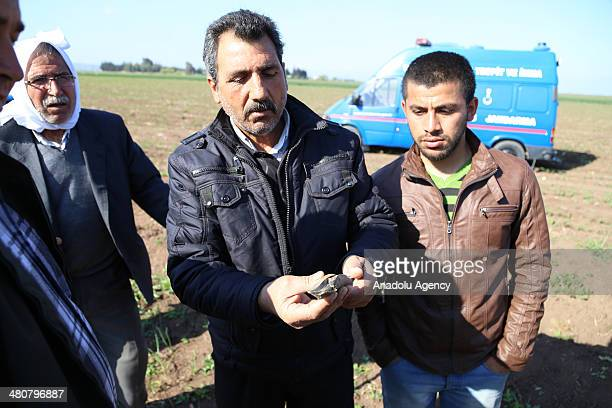 A citizen shows a piece of mortar shell following the mortar shells dropped on in an empty land Turkey's Reyhanli region close to the Syrian border...