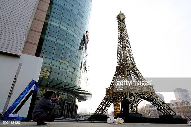 A citizen takes photoes of a 30meterhigh golden Eiffel Tower replica with cellphone on December 8 2015 in Shenyang Liaoning Province of China