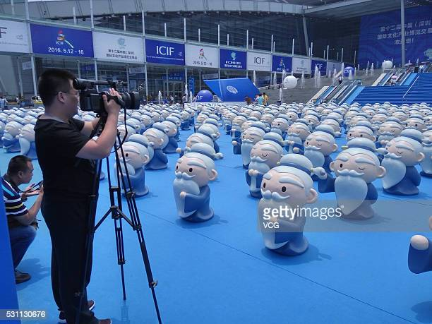 A citizen takes photos of cartoon Confucius figures displayed during the 12th China International Cultural Industry Fair at Shenzhen Convention...
