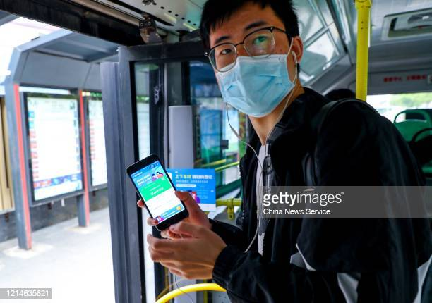 Citizen wearing face mask scans a QR code with smartphone to register real name before getting off a bus on March 25, 2020 in Wuhan, Hubei Province...