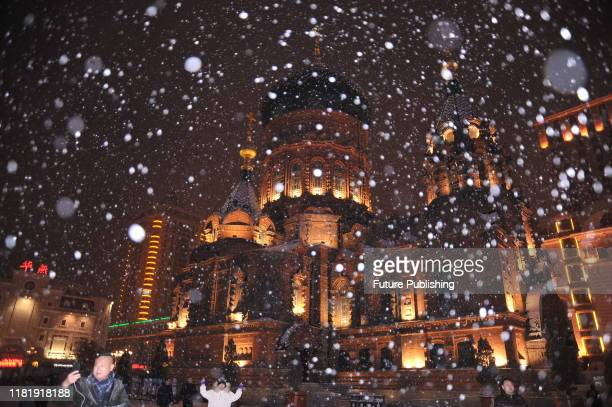 HARBIN CHINA NOVEMBER 12 2019 Citizens and tourists take photos and play in the snow during the first snow after the start of winter in Harbin...