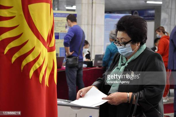 Citizens arrive at a polling station to cast their votes for Kyrgyzstan's parliamentary election, amid the ongoing novel coronavirus pandemic, in...