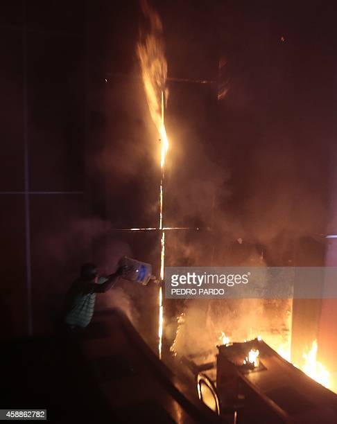 Citizens attempt to extinguish the fire at the state congress in Chilpancingo Guerrero State Mexico on November 12 2014 Demonstrators angry over the...