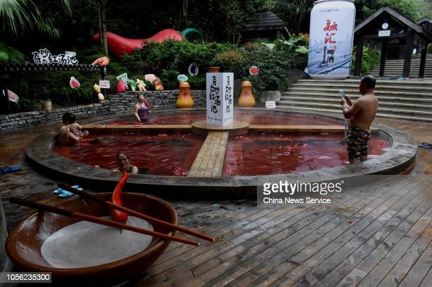 Citizens bath in a red hot spring in the shape of a giant hot pot at the Chongqing Ronghui Hot Spring Resort on October 18 2018 in Chongqing China A...