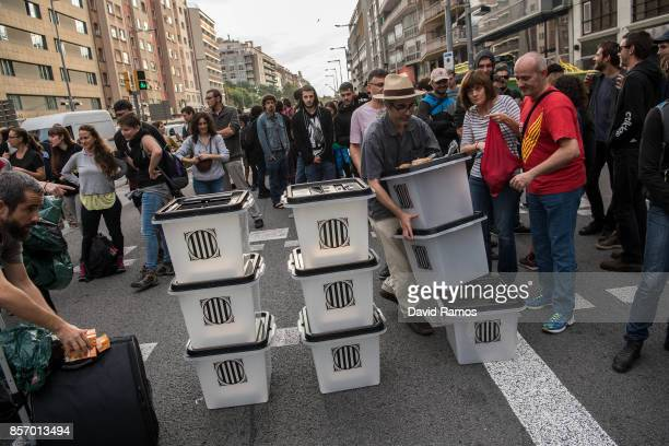 Citizens block a street with ballot boxes during a regional general strike to protest against the violence that marred Sunday's referendum vote on...