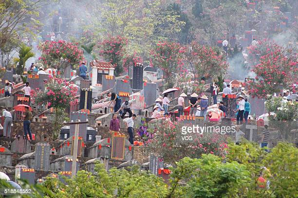 Citizens burn sacrifices and sweep tombs at a cemetery the day before Qingming Festival on April 3 2016 in Sanya Hainan Province of China The...