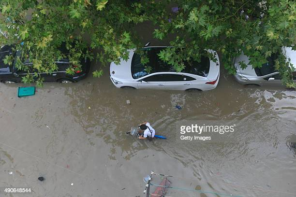 A citizens carries a bike while walking in ponding brought by the typhoon Dujuan in Jiangdong District on September 30 2015 in Ningbo Zhejiang...
