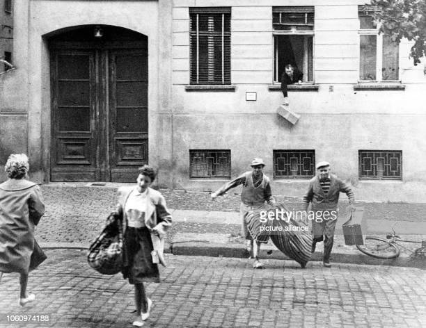 Citizens carry only few belongings as they flee to West Berlin after it became known, that GDR is separating East Berlin from West Berlin with barbed...