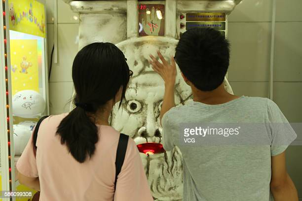 Citizens handle a fortunetell machine at an underground mall in People's Square on August 4 2016 in Shanghai China Only three coins one can receive a...