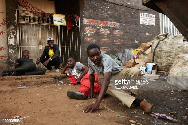 TOPSHOT Citizens hide from Zimbabwean soldiers in the streets of Harare on August 1 2018 after protests erupted over alleged fraud in the country's...