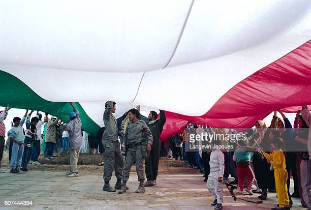 Citizens hold a giant Kuwaiti flag during a celebratory demonstration after the liberation of Kuwait City In August of 1990 Iraqi president Saddam...