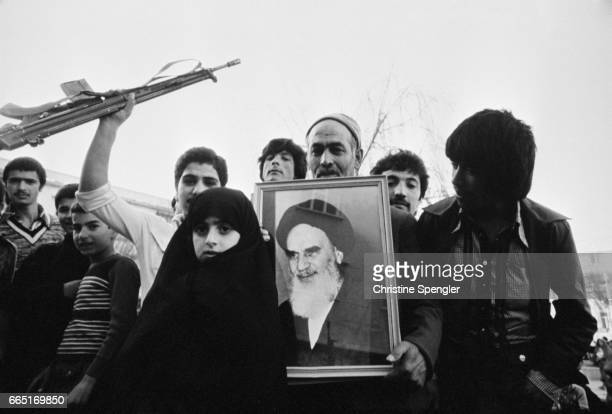 Citizens hold a portrait of Ruhollah Khomeini during a proKhomeini demonstration in Tehran