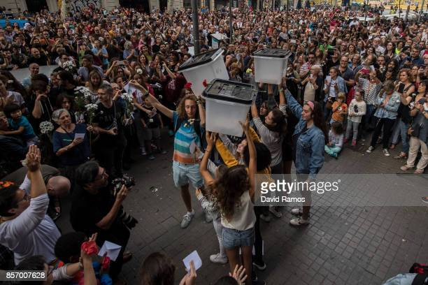 Citizens hold up ballot boxes during a tribute outside a school which acted as polling station in the referendum and was subsequently raided during a...