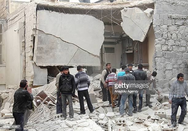 Citizens inspect the rubble of destroyed buildings following the barrel bombattacks of Syrian air forces on February 2 in Aleppo Syria More than 50...