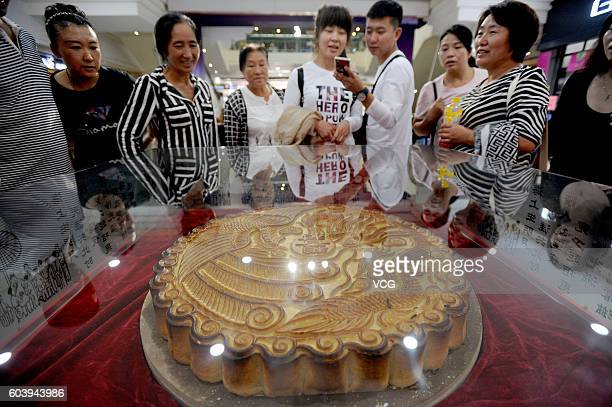 Citizens look a giant mooncake weighting fifty kilograms on September 13 2016 in Shenyang Liaoning Province of China The giant mooncake was made from...