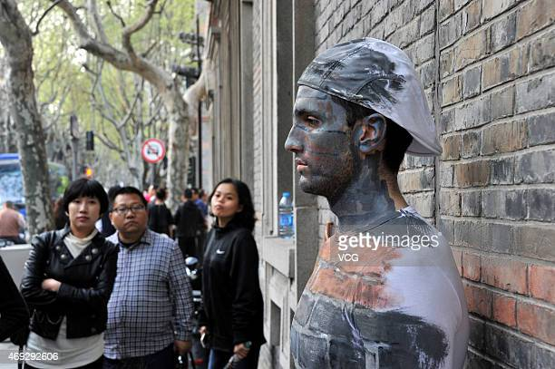 "Citizens look at a boy disguised as a wall near New World street on April 10, 2015 in Shanghai, China. A boy ""hides"" himself by being painted the..."