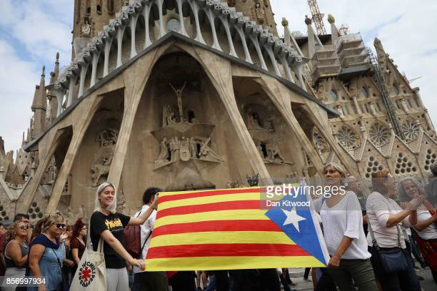 Citizens march with a Catalan flag during a regional general strike outside the Sagrada Familia which has been closed in protest against the violence...