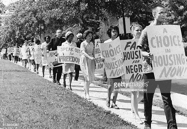 Citizens marching and holding signs during a protest during a conference for the National Association for the Advancement of Colored People 1964