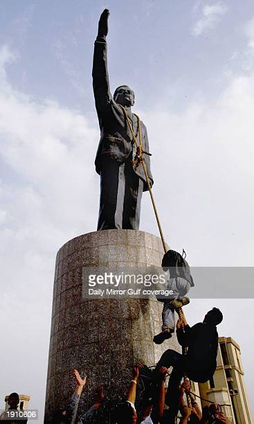 Citizens of Baghdad attempt to pull down a statue of Saddam Hussein in the centre of Baghdad April 9 2003