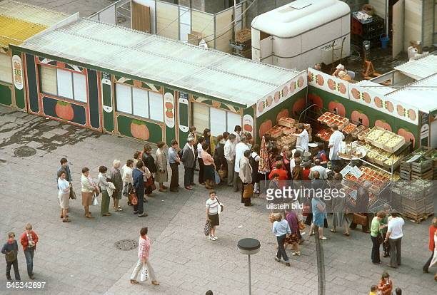 Citizens of East Berlin are queuing up at a veggie store on Alexanderplatz Square - around 1984