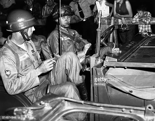 Citizens of Little Rock watch from behind barricades as members of the 101st Airborne Division arrive 9/24 to take up positions around Central High...
