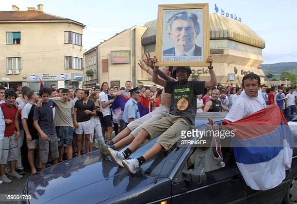 Citizens of the northern Bosnian town of Banja Luka display a portrait of Bopsnian Serb war crimes suspect fugitive Radovan Karadzic as they...