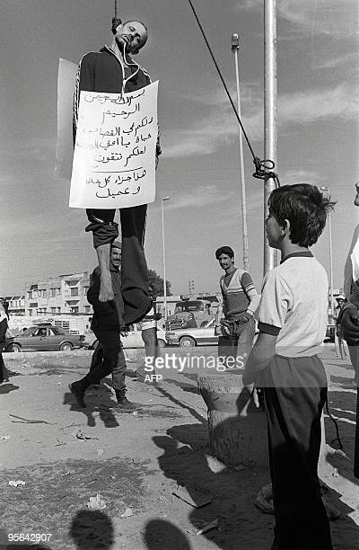 Citizens of the south Lebanese port of Sidon look at captain Mahmoud Hable who was hanged 30 October 1985 at a Sidon square after being accused of...