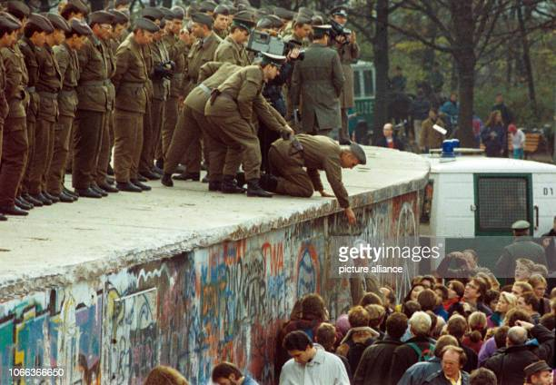 Citizens of West Berlin hand a pot of coffee to GDR border forces on the Berlin Wall Germany 11 November 1989 The Wall was opened in the night of...