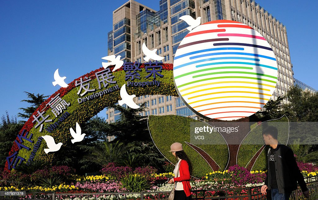 Citizens pass by the flower terrace for Asia-Pacific Economic Cooperation (APEC) at Changan Avenue on October 26, 2014 in Beijing, China. Flowers in the themes of 'Harmony and Win-win Result' and 'Peaceful Development' were arranged at Changan Avenue for the upcoming APEC summit on Thursday in Beijing.
