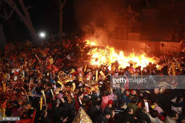 Citizens pray with incense sticks to celebrate the Lunar New Year marking the Year of the Dog at the Taihao Temple on February 16 2018 in Zhoukou...