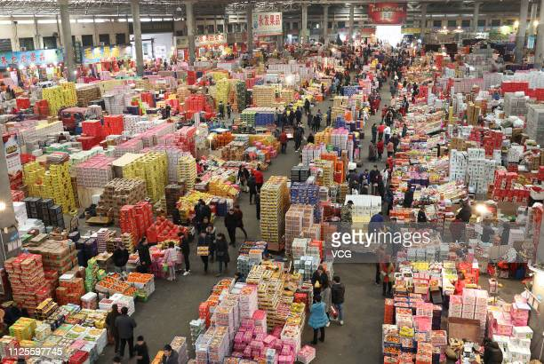 Citizens purchase fruit at a market to prepare for the Chinese New Year, the Year of the Pig, on January 28, 2019 in Yiwu, Zhejiang Province of...