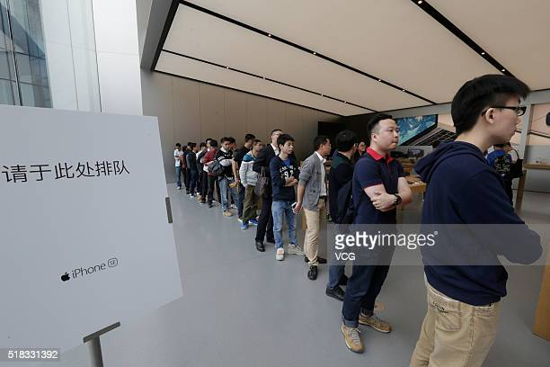 Citizens queue up outside an Apple Store as Apple launches its iPhone SE globally on Thursday on March 31 2016 in Guangzhou Guangdong Province of...