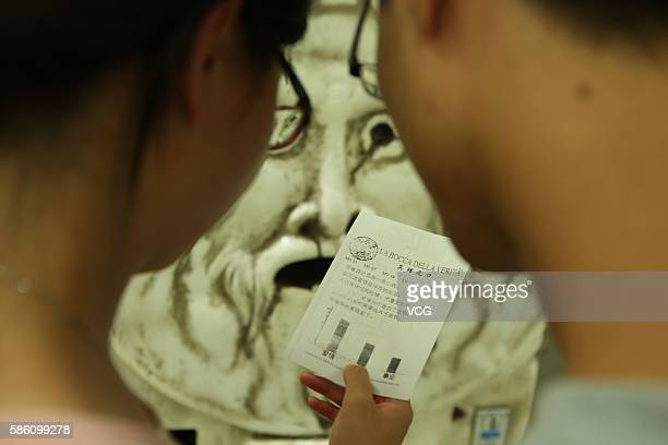 Citizens read a letter come from a fortunetelling machine at an underground mall in People's Square on August 4 2016 in Shanghai China Only three...