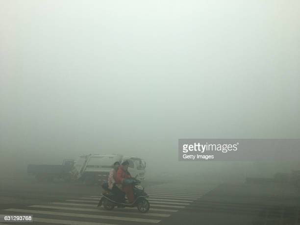 Citizens ride in the heavy smog on January 9, 2017 in Zhengzhou, Henan Province of China. The Central Meteorological Observatory issued a yellow...