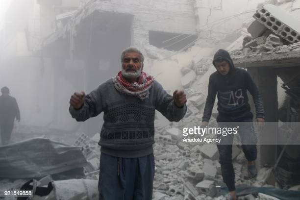 Citizens search and inspect the debris of buildings after Assad Regime carried out an airstrike over Arbin town of the Eastern Ghouta region which is...