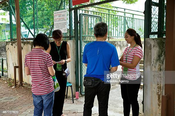 Citizens show their polling cards and identity cards to the presiding officers outside the Bedeck Green School one of the polling stations during the...